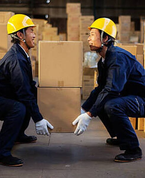 two men demonstrating safe manual handling by lifting a box